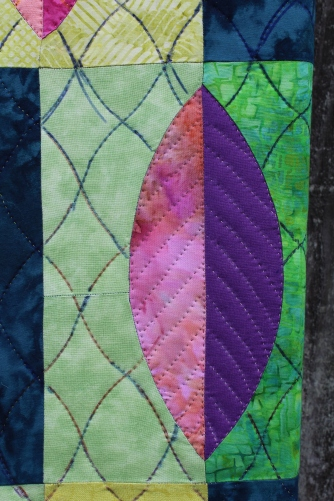 A close up of the hand quilting of a leaf.